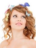 Muchacha adolescente feliz con las mariposas en pelo Imagen de archivo