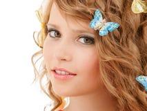 Muchacha adolescente feliz con las mariposas en pelo Fotos de archivo libres de regalías