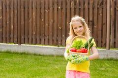 Muchacha adolescente feliz con las verduras en cesta Imágenes de archivo libres de regalías
