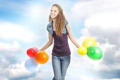 Muchacha adolescente feliz con los globos en fondo del cielo Imagen de archivo libre de regalías