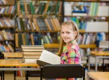 Muchacha adolescente feliz con mirada del libro detrás en biblioteca Fotografía de archivo
