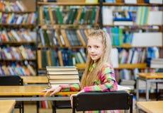 Muchacha adolescente feliz con mirada del libro detrás en biblioteca Imagen de archivo libre de regalías