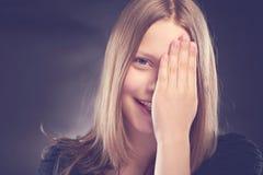 Muchacha adolescente feliz con su mano en cara Fotos de archivo libres de regalías