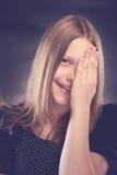 Muchacha adolescente feliz con su mano en cara Foto de archivo