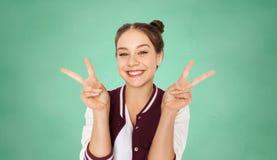 Muchacha adolescente feliz del estudiante que muestra el signo de la paz Foto de archivo libre de regalías