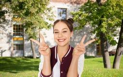 Muchacha adolescente feliz del estudiante que muestra el signo de la paz Fotos de archivo libres de regalías