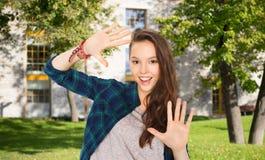 Muchacha adolescente feliz del estudiante que muestra las manos Fotografía de archivo libre de regalías