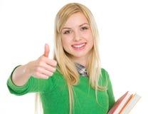 Muchacha adolescente feliz del estudiante que muestra los pulgares para arriba Fotos de archivo libres de regalías