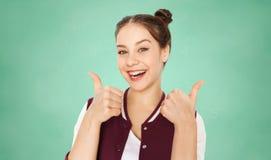Muchacha adolescente feliz del estudiante que muestra los pulgares para arriba Imagenes de archivo