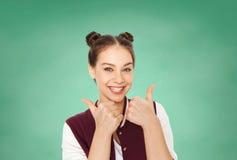Muchacha adolescente feliz del estudiante que muestra los pulgares para arriba Imagen de archivo libre de regalías