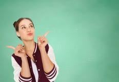 Muchacha adolescente feliz del estudiante sobre consejo escolar verde Imagen de archivo libre de regalías