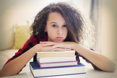 Muchacha adolescente feliz del pelo rizado que descansa sobre los libros Fotografía de archivo libre de regalías
