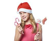 Muchacha adolescente feliz en casquillo rojo con el caramelo de la Navidad aislado Imagen de archivo libre de regalías