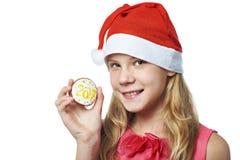 Muchacha adolescente feliz en casquillo rojo con la galleta de la Navidad aislada Fotos de archivo