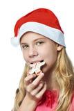 Muchacha adolescente feliz en casquillo rojo que come la galleta de la Navidad aislada Imagen de archivo