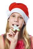Muchacha adolescente feliz en casquillo rojo que come la galleta de la Navidad aislada Foto de archivo
