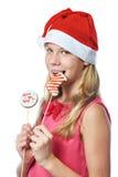 Muchacha adolescente feliz en casquillo rojo que come la galleta de la Navidad aislada Fotos de archivo