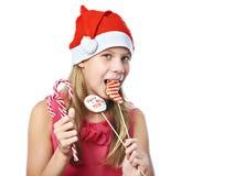 Muchacha adolescente feliz en casquillo rojo que come la galleta de la Navidad aislada Fotografía de archivo