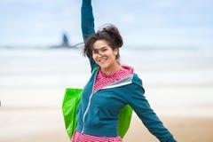 Muchacha adolescente feliz en chaqueta azul en la playa, brazos extendidos Fotografía de archivo libre de regalías