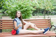 Muchacha adolescente feliz en el banco Fotos de archivo libres de regalías