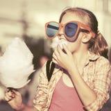 Muchacha adolescente feliz en gafas de sol que come el caramelo de algodón en calle de la ciudad Fotografía de archivo