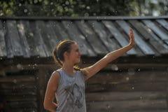 Muchacha adolescente feliz en la lluvia del verano Foto de archivo