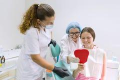 Muchacha adolescente feliz en silla dental Concepto de la medicina, de la odontología y de la atención sanitaria foto de archivo