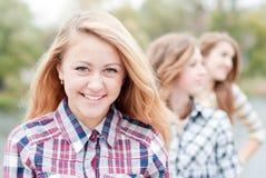 Muchacha adolescente feliz joven con los amigos Imágenes de archivo libres de regalías