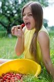 Muchacha adolescente feliz joven que come la fresa Imágenes de archivo libres de regalías