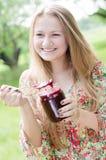Muchacha adolescente feliz joven que come la mermelada de fresa Foto de archivo libre de regalías