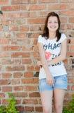 Muchacha adolescente feliz joven que se coloca en el copyspace del fondo de la pared de ladrillo Fotos de archivo