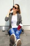 Muchacha adolescente feliz joven que usa un teléfono elegante sobre la pared en el backg Imagen de archivo