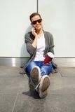 Muchacha adolescente feliz joven que usa un teléfono elegante sobre la pared en el backg Fotografía de archivo libre de regalías