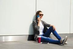 Muchacha adolescente feliz joven que usa un teléfono elegante sobre la pared en el backg Imágenes de archivo libres de regalías