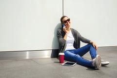Muchacha adolescente feliz joven que usa un teléfono elegante sobre la pared en el backg Fotos de archivo