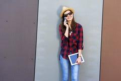 Muchacha adolescente feliz joven que usa un teléfono elegante, tableta sobre la pared en t Foto de archivo