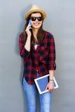 Muchacha adolescente feliz joven que usa un teléfono elegante, tableta sobre la pared en t Imagenes de archivo
