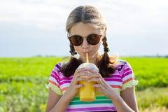 Muchacha adolescente feliz que bebe el zumo de naranja en el día de verano caliente Fotografía de archivo