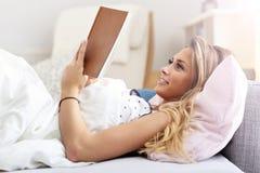 Muchacha adolescente feliz que descansa sobre cama mientras que lee su libro nuevo preferido Foto de archivo libre de regalías