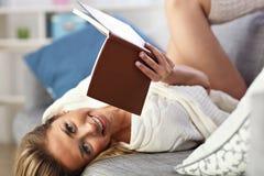 Muchacha adolescente feliz que descansa sobre el sofá en la sala de estar mientras que lee su libro nuevo preferido Imágenes de archivo libres de regalías