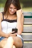 Muchacha adolescente feliz que escucha la música en smartphone Fotografía de archivo libre de regalías