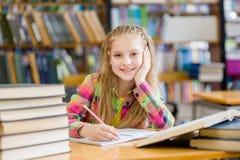 Muchacha adolescente feliz que estudia en la biblioteca Imagen de archivo libre de regalías