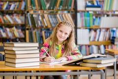 Muchacha adolescente feliz que estudia en la biblioteca Fotografía de archivo libre de regalías