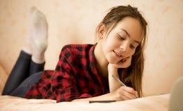 Muchacha adolescente feliz que miente en cama y que escribe en diario Fotografía de archivo libre de regalías