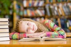 Muchacha adolescente feliz que miente en la tabla en biblioteca Fotografía de archivo