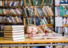Muchacha adolescente feliz que miente en la tabla en biblioteca Imagen de archivo libre de regalías