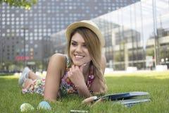 Muchacha adolescente feliz que miente en su estómago en la hierba Imagenes de archivo