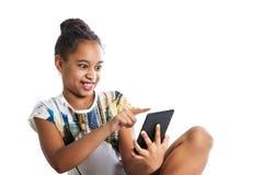 Muchacha adolescente feliz que mira la pantalla de la tableta Foto de archivo