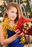 Muchacha adolescente feliz que mira sobre su regalo de la Navidad Imagenes de archivo