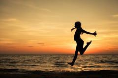 Muchacha adolescente feliz que salta en la playa Imagenes de archivo